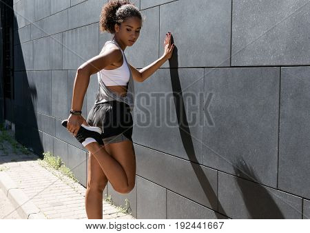Woman in sports clothes stretching before a workout
