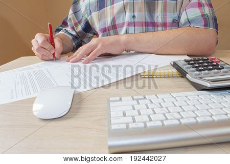 Businessman working on office desk with Calculator a computer a pen and papers. Businesses concept