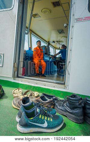 BALI, INDONESIA - APRIL 05, 2017: Different shoes waitting outside of the ferry boat pilot command cabin with view on the sea.