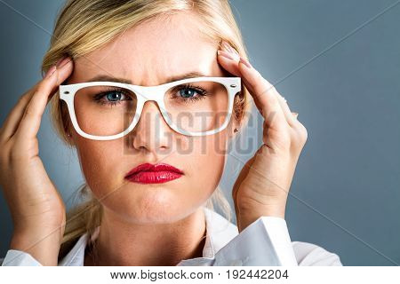 Young woman feeling stressed on a gray background