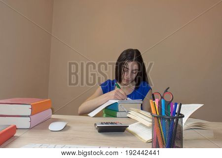 Young student with thoughtful expression sitting at a desk on some books. Education and school concept - little student girl with many books