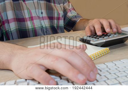 Businessman hand using calculator accounting concept. Man hands with pencil notebook and Calculator on wooden table