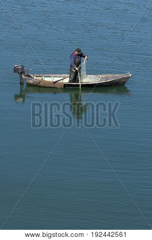 Fisherman at estuary of river Neretva pulling net from water