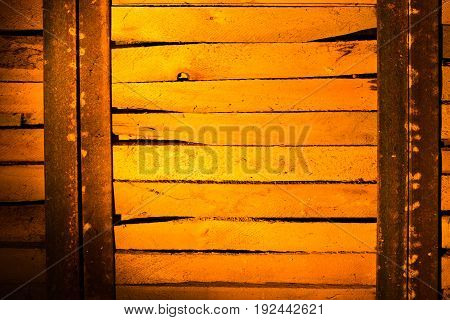 Wooden boards in golden lighting as background .