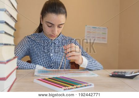Young Girl is working with atlas at the wood table. Education and school concept - little student girl with many books