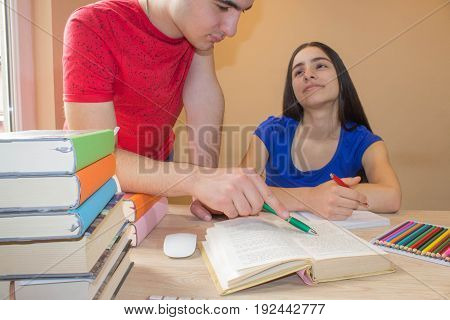 Older brother helping young sister with writing lesson. Education and school concept