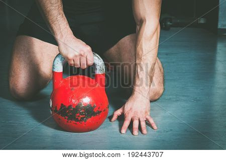 Man holding kettle bell with his hand on the gym floor. Kettle bell training workout.