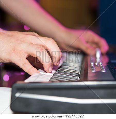 Musician plays keyboards in a rock band.