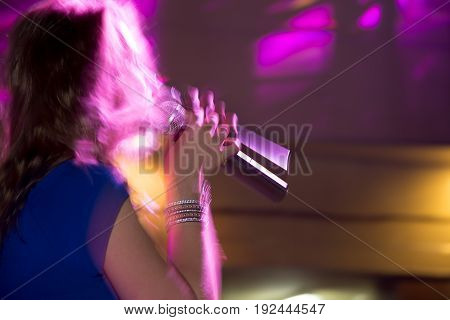 The girl sings into the microphone on stage .
