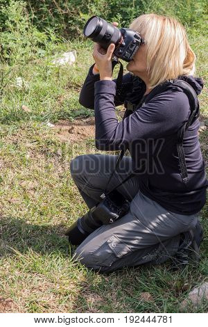 Nilgiri Hills India - October 26 2013: Kneeled blonde photographer takes picture in Masamigulli Forest. She holds two heavy DLRS cameras. Face hidden.