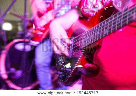 Musician playing guitar in a rock band .