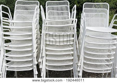 View on white Garden Chairs. Close-up of stacked Lawn Chairs.