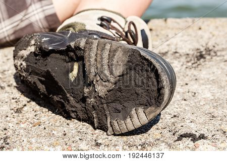Outdoor trip holidays relax footwear concept. Checking on worn out shoe. Person with destroyed old boot.