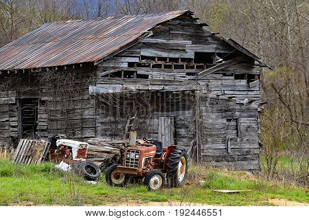 An old abandoned barn with tractors out front in North Carolina