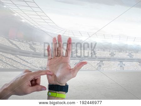 Digital composite of Hand counting with a sports stadium