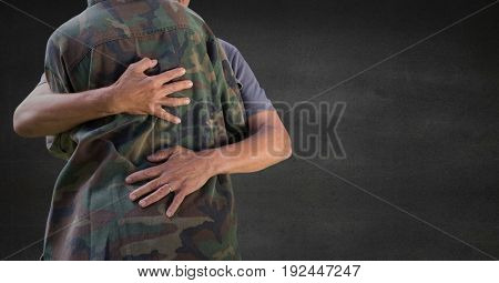 Digital composite of Back of soldier hugging against grey wall