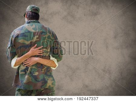 Digital composite of Back of soldier hugging with grunge overlay against brown background