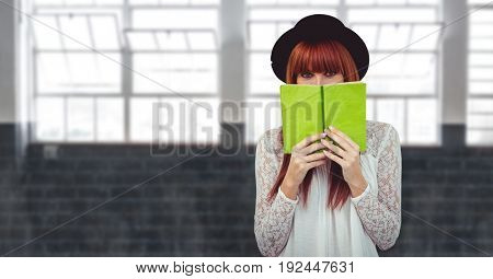 Digital composite of Female hipster covering face with book