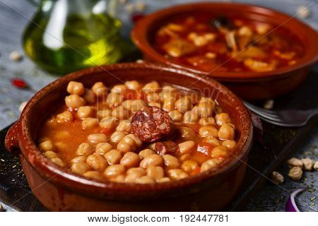 closeup of an earthenware bowl with potaje de garbanzos, a chickpeas stew with chorizo and serrano ham, and a bowl with callos, a typical beef tripe stew in the background