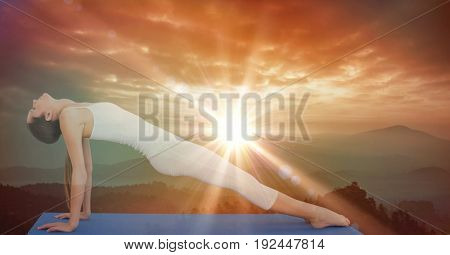 Digital composite of Side view of flexible woman performing yoga during sunset