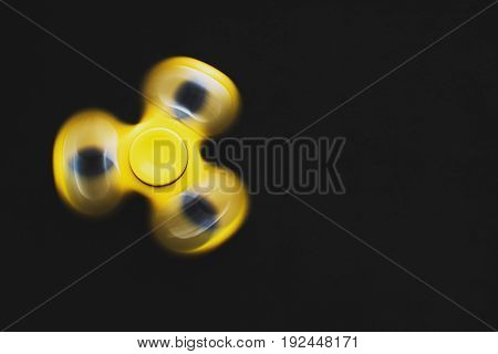 Rotating Yellow Fidget Spinner Device On Black Background. Top View. Playing With A Yellow Hand Spin