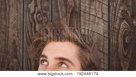 Digital composite of Male hipster looking away against wooden wall
