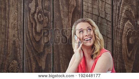 Digital composite of Happy woman using smart phone against wooden wall