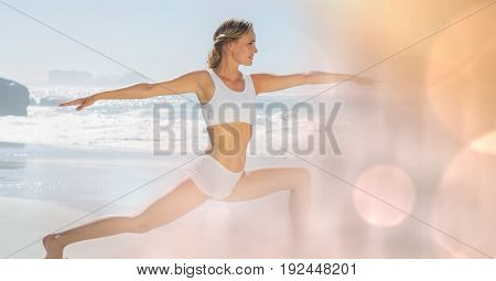 Digital composite of Fit young woman practicing yoga at beach