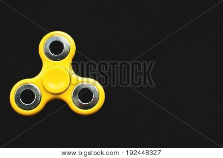 Yellow Fidget Spinner Device On Black Background. Top View. Playing With A Yellow Hand Spinner Fidge