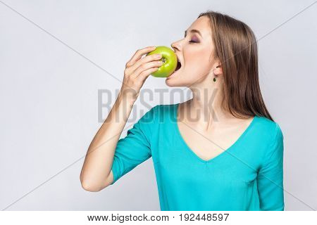 Young beautiful woman with freckles and green dress holding apple and eating with closed eyes. studio shot isolated on light gray background.