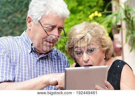 Portrait of an elderly couple using digital tablet. Outdoors.