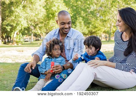 Happy family smiling and having fun outdoors. Young latin boy with brother and parents playing with soap bubbles at park. Multiethnic parents watching children enjoying making soap bubbles.