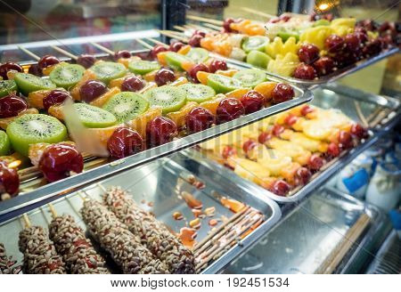 Shanghai, China - Nov 4, 2016: Night scene along Nanjing Road Pedestrian Street - Image shot through glass cabinet of some freshly prepared fruits and other snacks. Low-light street photography.