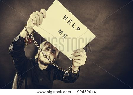 Stress depression assistance concept. Scared man with chained hands holding help me sign studio shot on dark grunge background sepia