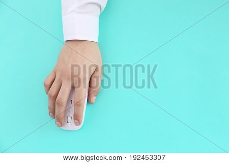 Male hand with computer mouse on color background