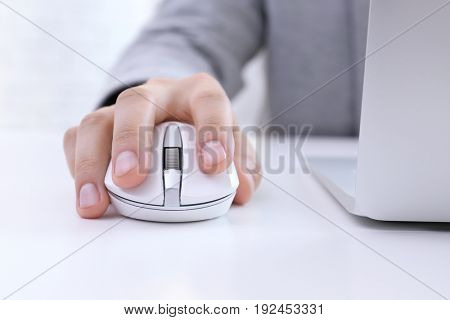 Male hand with computer mouse on table
