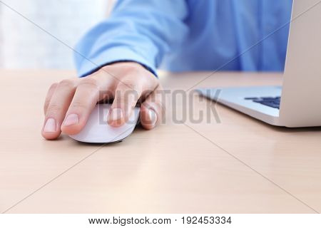 Male hand with computer mouse and laptop on table