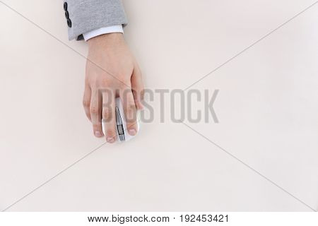 Male hand with computer mouse on light background