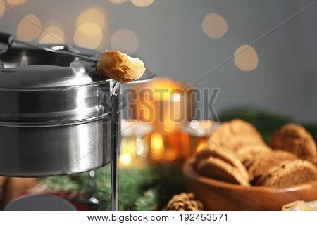 Fondue pot and piece of bread on blurred background