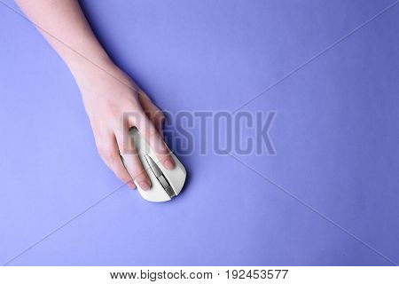 Female hand holding computer mouse on color background