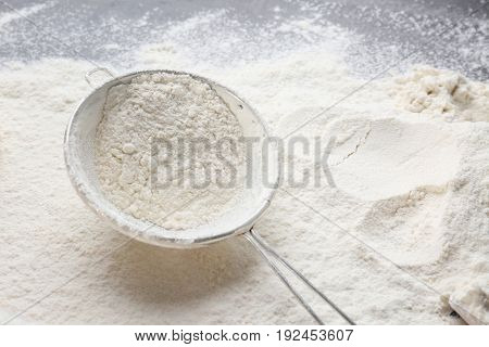Sieve with flour on kitchen table