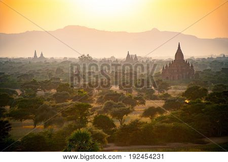 Beautiful ancient pagoda field in sun rise with fog and haze
