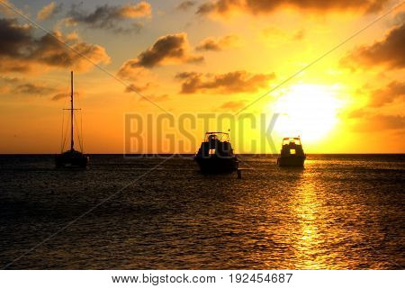 Beautiful sunset at the sea with three small boats