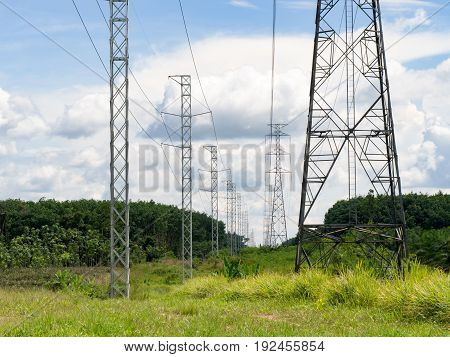 High voltage electric power pole in green field against with blue sky white cloud.