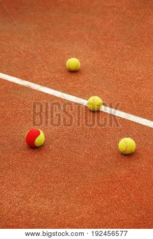 Three yellow and one red-yellow tennis balls lie on the tennis court. The concept of sport. Be different.