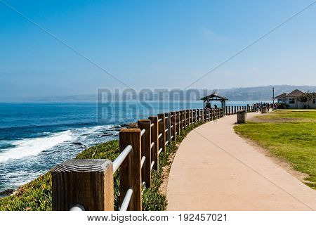 LA JOLLA, CALIFORNIA - JUNE 16, 2017:  Sidewalk leading to an observation point where people enjoy the ocean views of La Jolla Cove from Ellen Browning Scripps Park.
