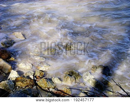Soft relaxing waves on a rocky beachside White foaming waves break against small rocks at a beach in a tropical island