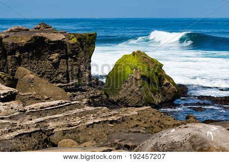 Eroded natural sandstone rock formations at La Jolla Cove in San Diego County with ocean waves in the background.