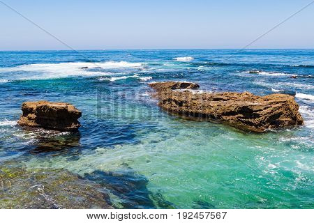 Blue and green water surrounds natural rock formations in the ocean at La Jolla Cove in San Diego County.