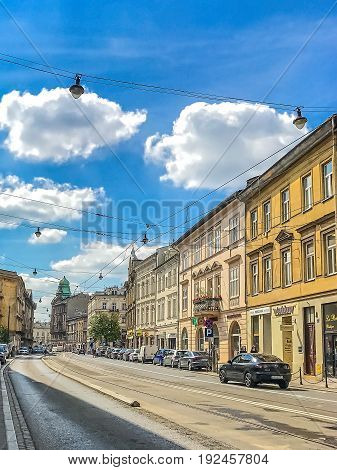 KRAKOW, POLAND - June 15, 2017: A street with ancient apartment buildings and other monuments in central Kraków, Poland.